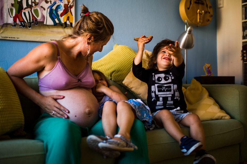 Pregnant mom playing with her children.