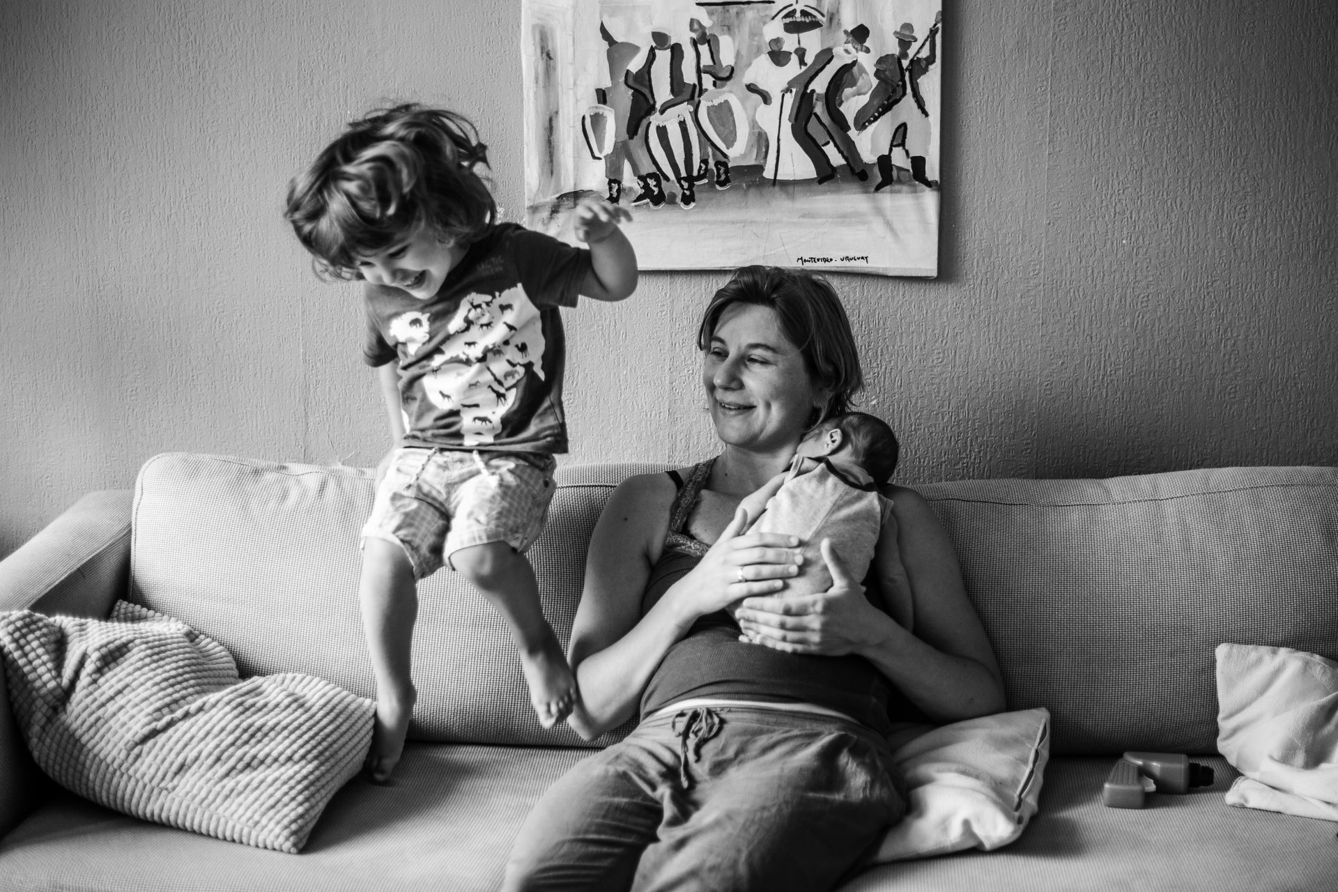 Mom holding her newborn in her chest sitting on the couch while her toddler is jumping on it next to her. Documentary photoshoot in Amsterdam.