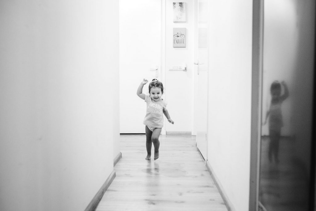 Documentary photography, toddler running in the kitchen