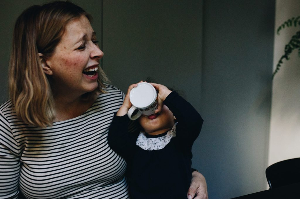mom laughing while her toddler is drinking yogurth