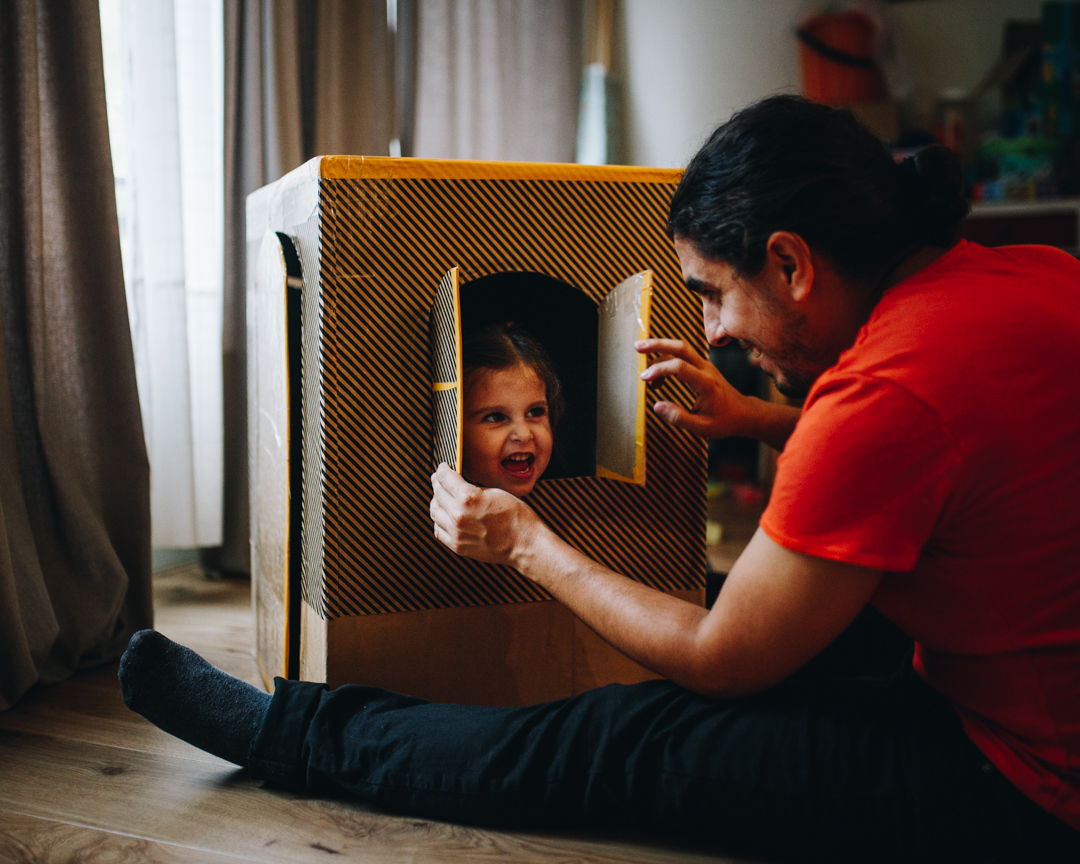 Little girl inside a cardboard house, playing with her father during a Documentary Family Photoshoot in Amsterdam