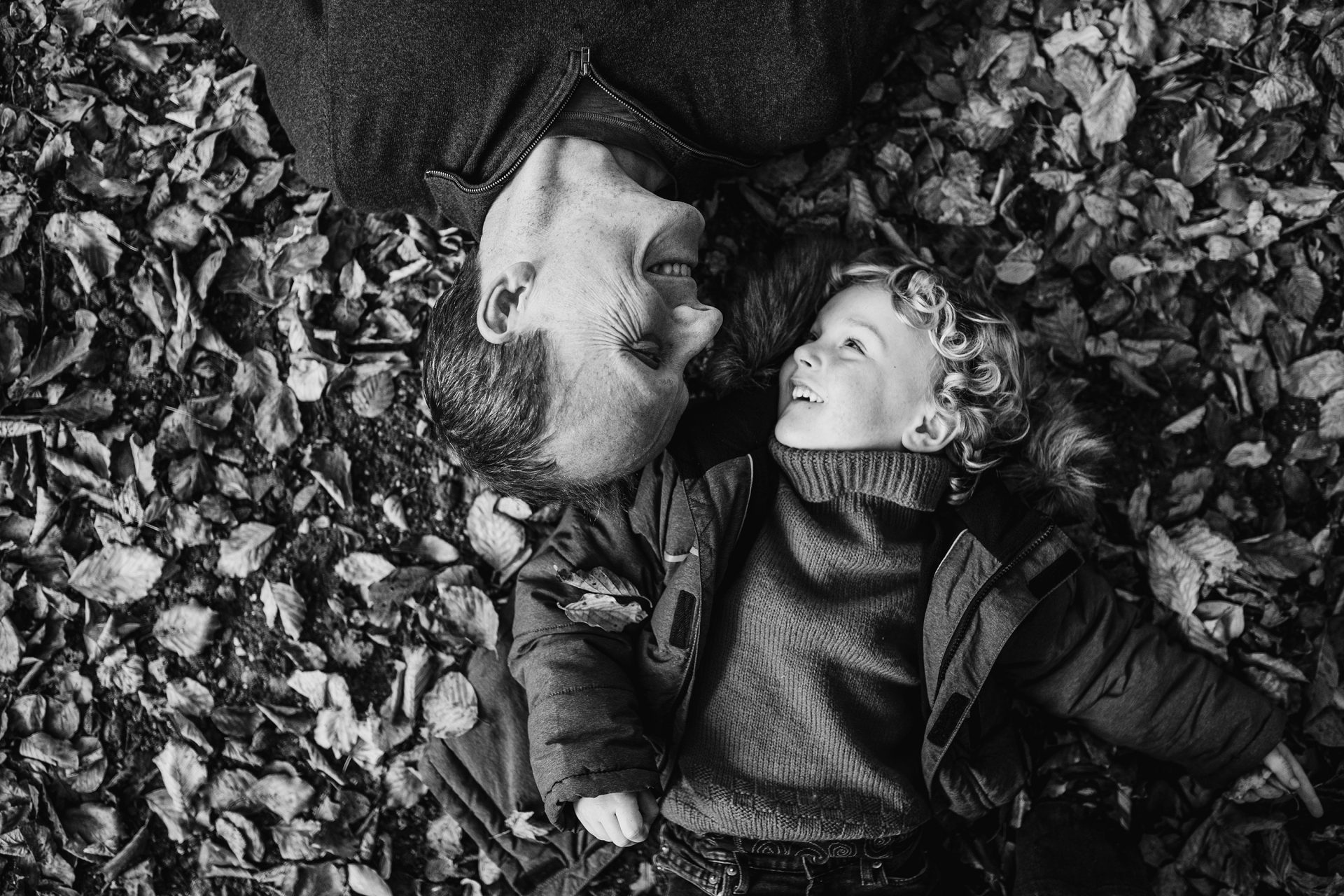 dad and son on the forest, lying on the leaves, looking at each other upside down. Black and white picture. Family photo shoot Leiden, Netherlands