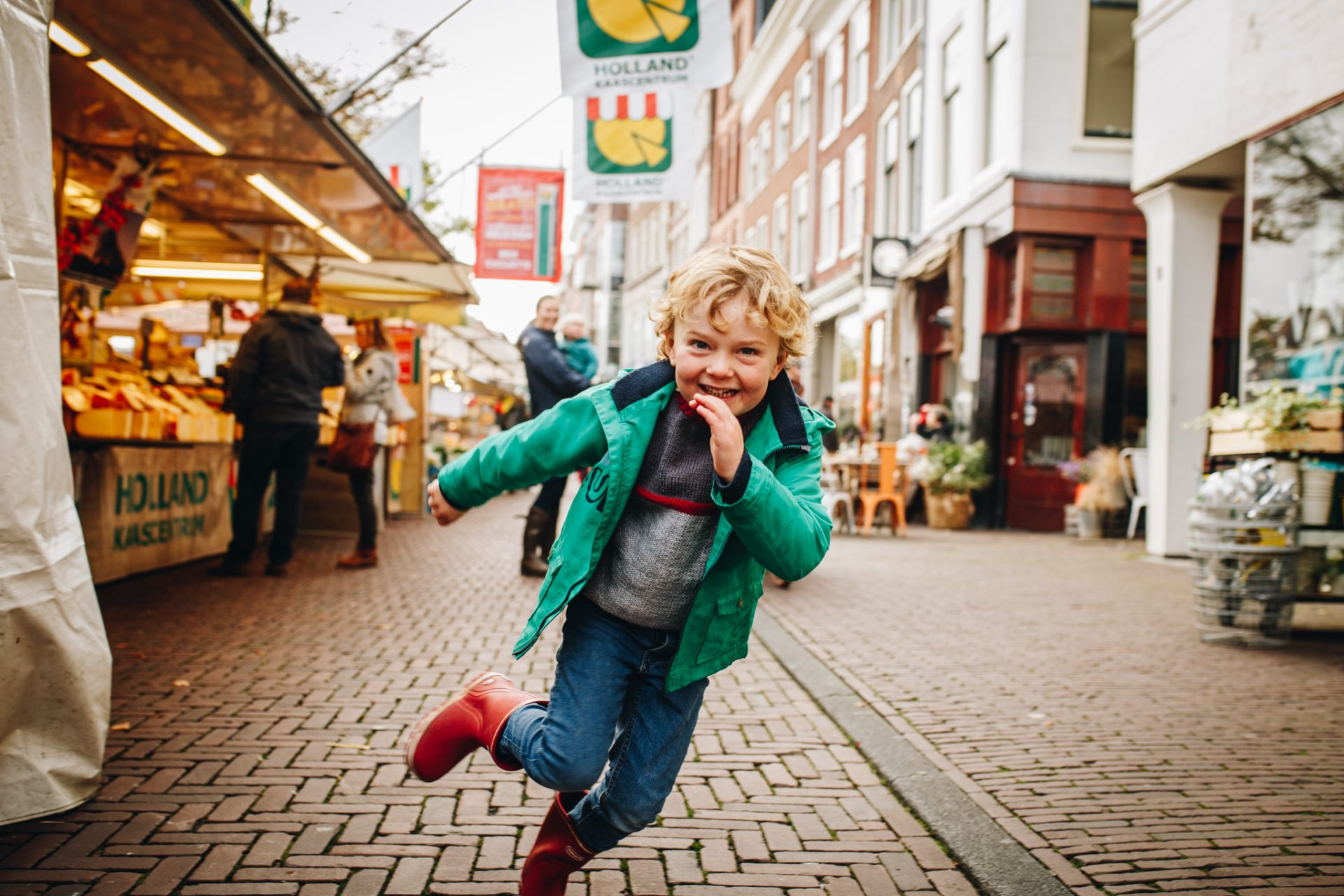 kid running towards me at the street market. He's smiling.