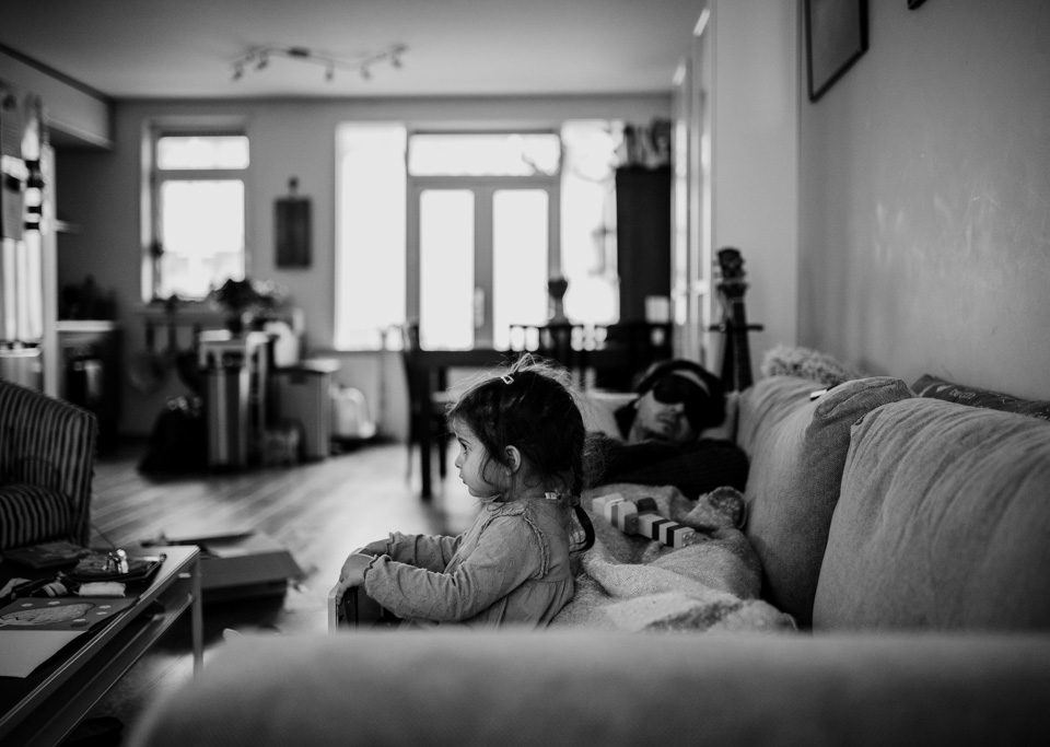 little girl watching TV while her father is sleeping next to her
